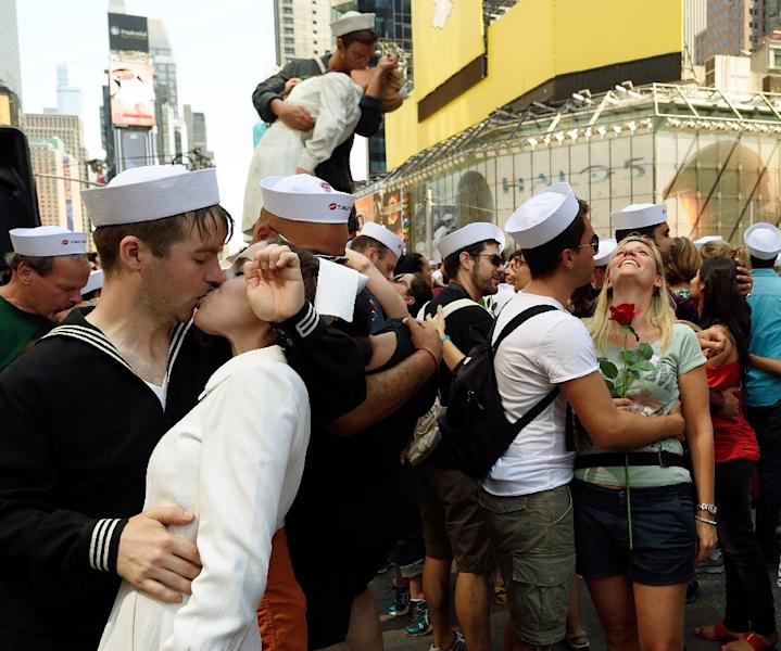 Couples, some dressed as sailors and nurses, embrace in Times Square on August 14, 2015 in New York (AFP Photo/Don Emmert)
