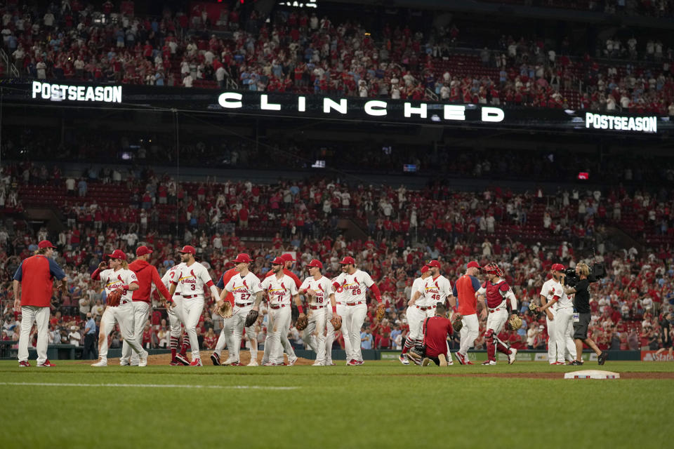 Members of the St. Louis Cardinals celebrate after defeating the Milwaukee Brewers in a baseball game to clinch a playoff spot Tuesday, Sept. 28, 2021, in St. Louis. (AP Photo/Jeff Roberson)