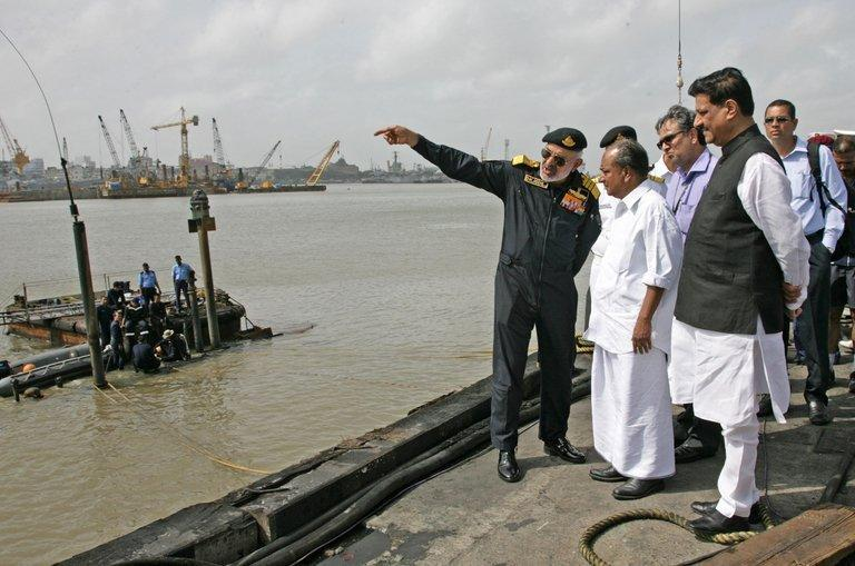 In this photo, released by the Ministry of Defence, Chief for Indian Naval Staff, Admiral D.K. Joshi (L), briefs Defence Minister A.K. Antony (C) at the scene of the stricken INS Sindhurakshak, after the submarine sank following an explosion at the naval dockyard, in Mumbai, on August 14, 2013. All 18 sailors on board of the submarine are feared dead