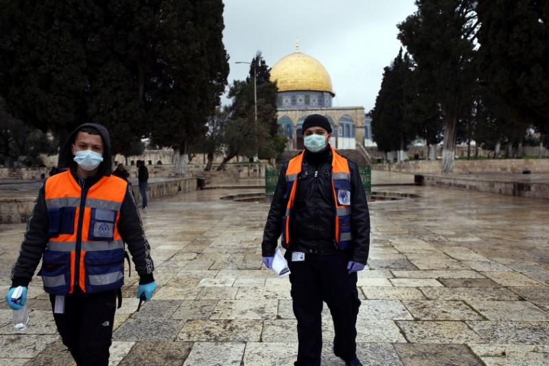 Palestinian volunteers, ready to offer cleaning gel to worshippers, walk in front of the Dome of the Rock in the compound known to Muslims as Noble Sanctuary and to Jews as Temple Mount, in Jerusalem's Old City