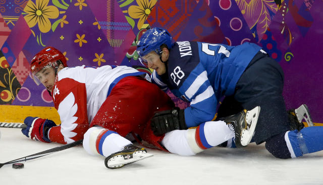 Finland forward Lauri Korpikoski crashes into Russia defenseman Alexei Yemelin during the second period of a men's quarterfinal ice hockey game at the 2014 Winter Olympics, Wednesday, Feb. 19, 2014, in Sochi, Russia. (AP Photo/Mark Humphrey)