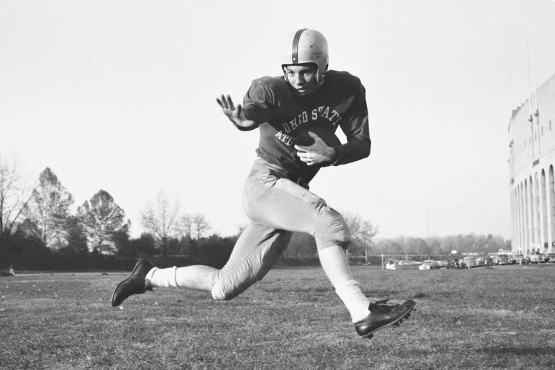 """FILE - This 1953 file photo, shows Ohio State halfback Howard """"Hopalong"""" Cassady in action pose in Columbus, Ohio. Cassady, a Heisman Trophy winner and former NFL running back, died early Friday, Sept. 20, 2019, in Tampa, Fla.,  Jerry Emig, the Ohio State associate athletic director said. He was 85. Cassady played both football and baseball at Ohio State in the early 1950s, winning the Heisman Trophy in 1955. He also played 10 seasons in the NFL, mostly with the Detroit, and got the nickname """"Hopalong"""" from local sports writers after the black-hatted Western star of the 1950s. (AP Photo/Harold Valentine, File)"""