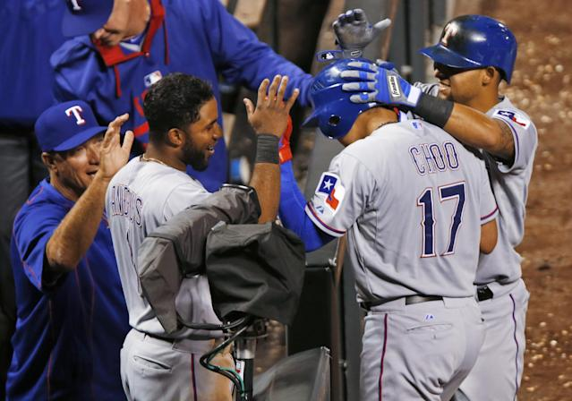 Texas Rangers' Shin-Soo Choo (17) is congratulated by, from left, manager Jeff Banister, Elvis Andrus and Rougned Odor after Choo scored on a single by Robinson Chirinos in the ninth inning of s baseball game against the Colorado Rockies pm Tuesday, July 21, 2015, in Denver. Choo tripled to lead of the inning to complete the cycle. Texas won 9-0. (AP Photo/David Zalubowski)
