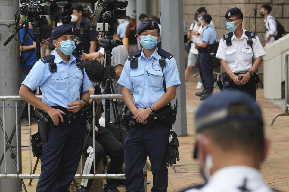 Police officers stand guard outside a court Friday, July 30, 2021, in Hong Kong, as a pro-democracy demonstrator Tong Ying-kit exits the court after his sentencing for the violation of a security law during a 2020 protest. Tong has been sentenced to nine years in prison in the closely watched first case under Hong Kong's national security law as Beijing tightens control over the territory. (AP Photo/Vincent Yu)
