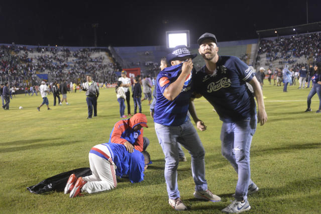 Soccer fans gather on the field in an attempt to escape tear gas that was fired by police who were trying to break up a deadly fight between fans before the start of a game between Motagua and Olimpia, at the national stadium in Tegucigalpa, Honduras, late Saturday, Aug. 17, 2019. The fight between fans of rival soccer teams outside the stadium left three people dead and led to the suspension of the game. (Victor Colindres/La Tribunal via AP)