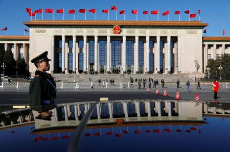 A paramilitary policeman stands guard in front of the Great Hall of the People at the Tiananmen Square ahead of a planery session of the National People's Congress in Beijing