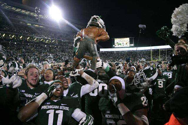 Michigan State players celebrate with the Paul Bunyon Trophy following their 29-6 win over Michigan in an NCAA college football game, Saturday, Nov. 2, 2013, in East Lansing, Mich. (AP Photo/Al Goldis)