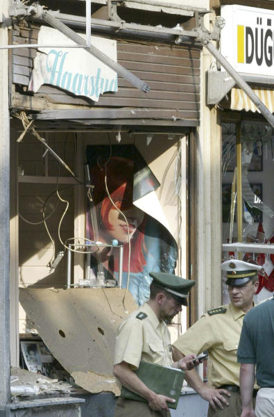 FILE - In this June 9, 2004 file picture police officers stand in front of a hairdressers shop at the scene of a bomb blast in Cologne, western Germany. Beate Zschaepe, the sole survivor of a neo-Nazi group _ the self-styled National Socialist Underground _ blamed for ten killings goes on trial Monday, May 6, 2013 in Munich, along with four men alleged to have helped the killers in various ways. Beate Zschaepe, 38, is charged with complicity in the murder of eight Turks, a Greek and a policewoman. She is also accused of involvement in at least two bombings and 15 bank robberies carried out by her accomplices Uwe Mundlos and Uwe Boenhardt, who died in an apparent murder-suicide two years ago (AP Photo/Hermann J. Knippertz,File)EARLY RISER FOR FRIDAY MAY 3 2013 -