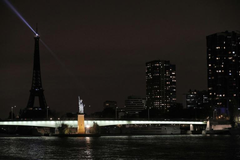 The statue of liberty replica in Paris is illuminated here against a dark background.