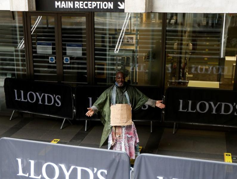 Demonstrator Clapper Priest protests in front of the Lloyd's building in the City of London financial district, in London