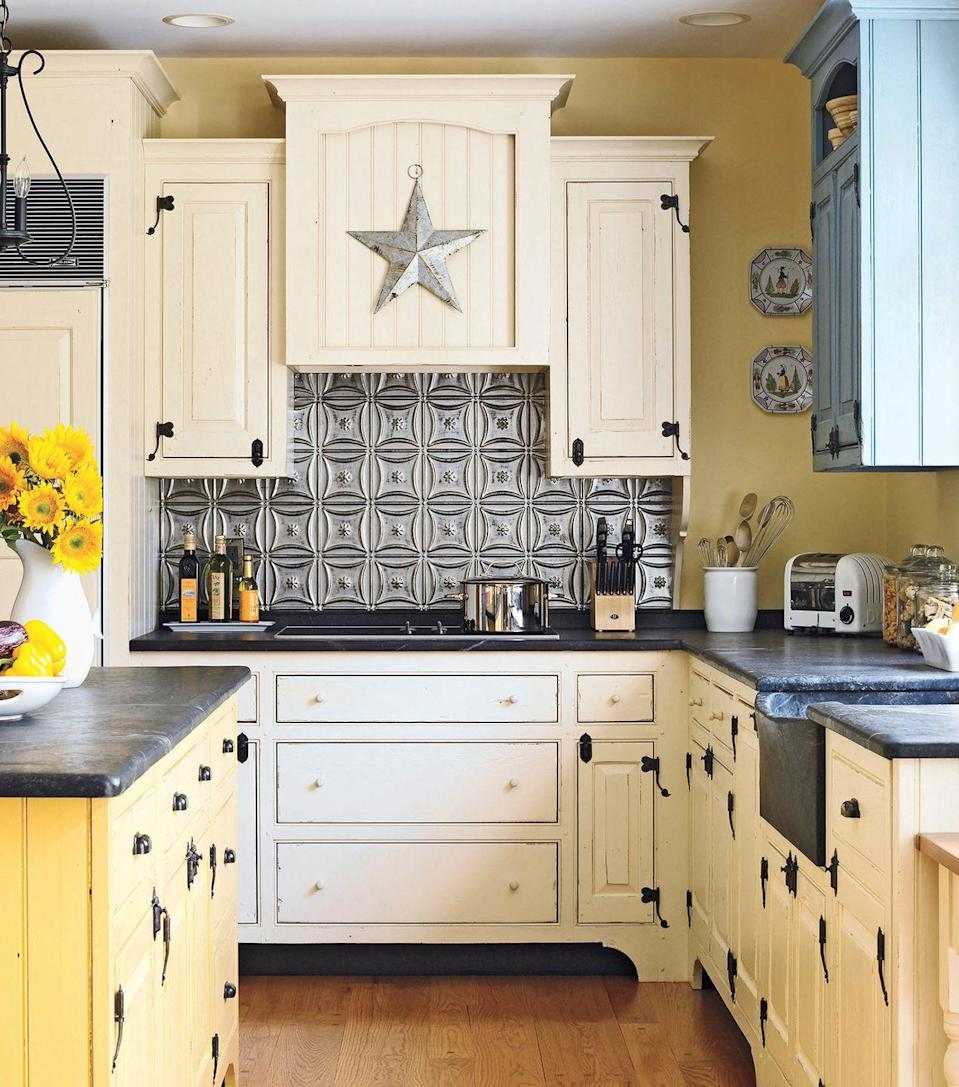<p>Not only does this kitchen's cream cabinets add to its fun vibe — a textured silver backsplash gives it a contemporary feel.</p>