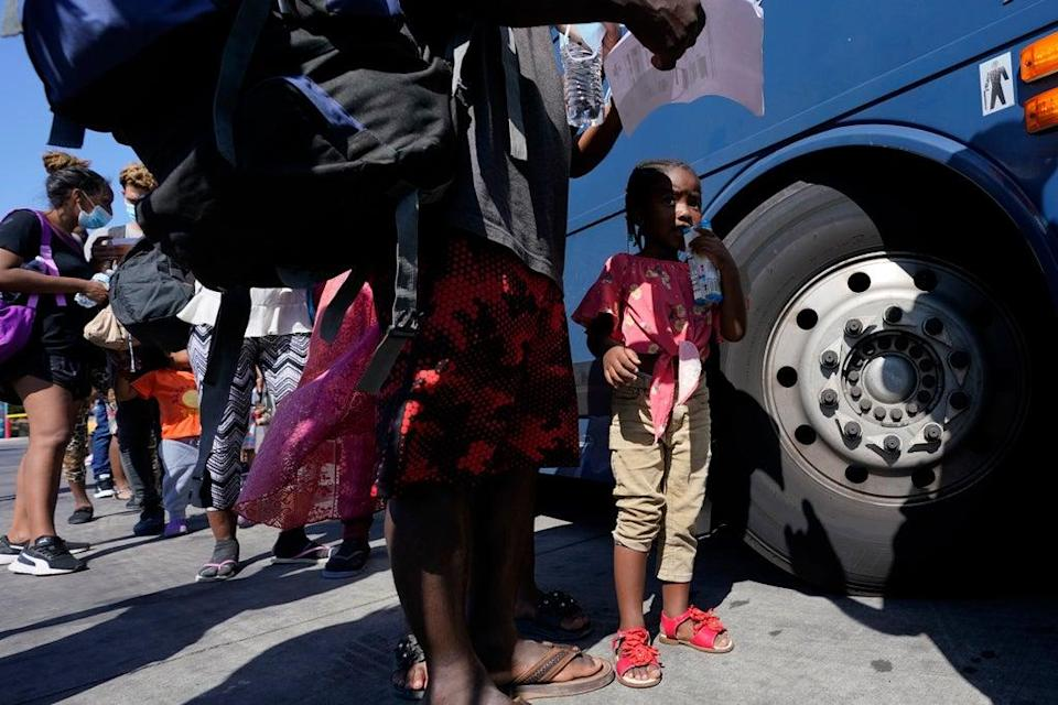 Migrants, many from Haiti, board a bus after they were processed and released after spending time at a makeshift camp near the International Bridge, Monday, 20 September 2021, in Del Rio, Texas (AP)