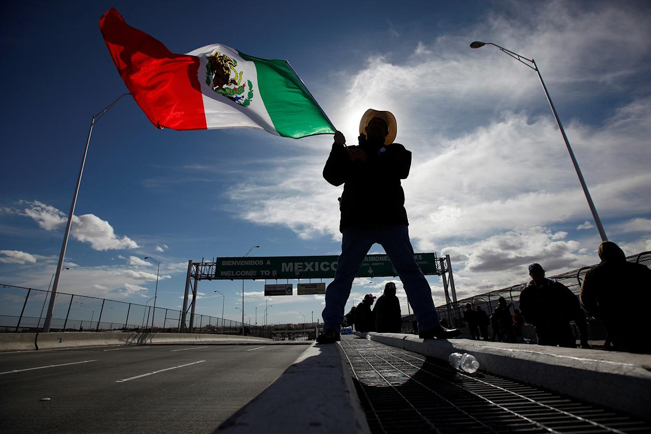 <p>A farmer waves a Mexican flag while blocking the Bridge of the Americas border crossing between Ciudad Juarez, Mexico and El Paso, U.S., during a protest against a fuel price hike in Ciudad Juarez, Mexico January 20, 2017. (REUTERS/Jose Luis Gonzalez) </p>