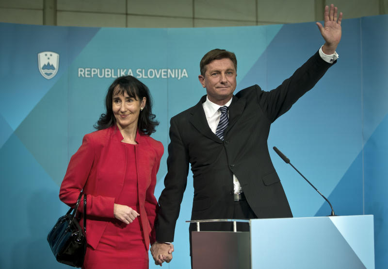 President elect, Slovenia's former prime minister Borut Pahor, right, with his spouse Tanja Pecar waves to the media in Ljubljana, Slovenia, Sunday, Dec. 2, 2012.  Pahor, who has called for unity in the tiny EU nation amid growing discontent with government tax hikes and spending cuts, won the presidential election. (AP Photo/Darko Bandic)