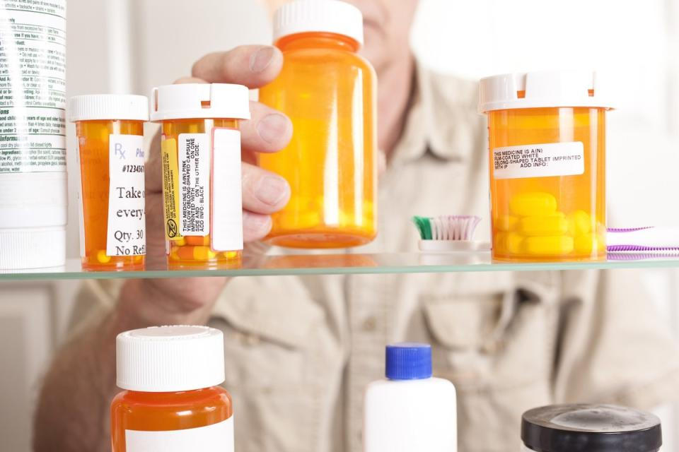 Senior adult man gets prescription medicines out of his medicine cabinet