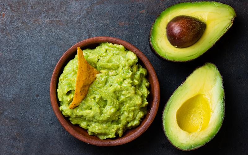 Traditional latinamerican mexican sauce guacamole in clay bowl and avocado sandwiches on dark background. Top view