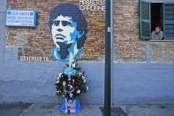 A woman looks out of a window as flowers commemorating soccer legend Diego Maradona are placed beneath a mural depicting him, in Naples, southern Italy, Thursday, Nov. 26, 2020. Maradona died Wednesday, Nov. 25, 2020 in Buenos Aires. (AP Photo/Alessandra Tarantino)