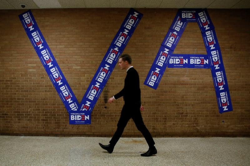 A man walks past campaign signs decorating a wall before the start of a campaign event with Democratic U.S. presidential candidate and former U.S. Vice President Joe Biden at Booker T. Washington High School in Norfolk, Virginia, U.S., March 1, 2020. REUTERS/Elizabeth Frantz