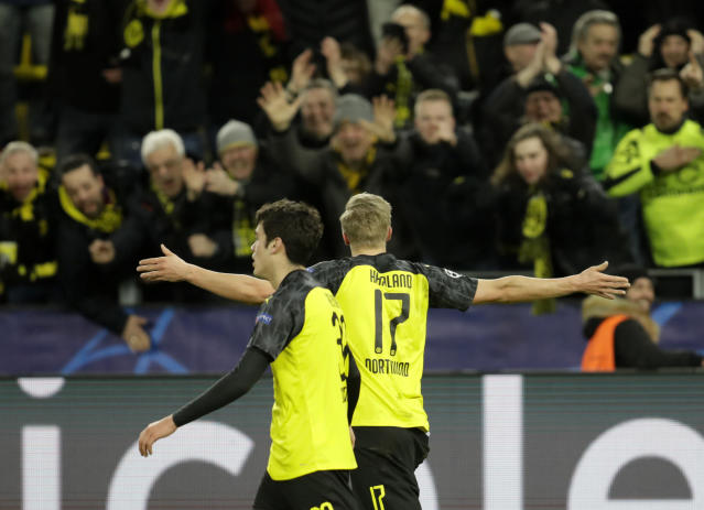 Dortmund's Erling Braut Haaland, right, celebrates after scoring his side's second goal during the Champions League round of 16 first leg soccer match between Borussia Dortmund and Paris Saint Germain in Dortmund, Germany, Tuesday, Feb. 18, 2020. (AP Photo/Michael Probst)