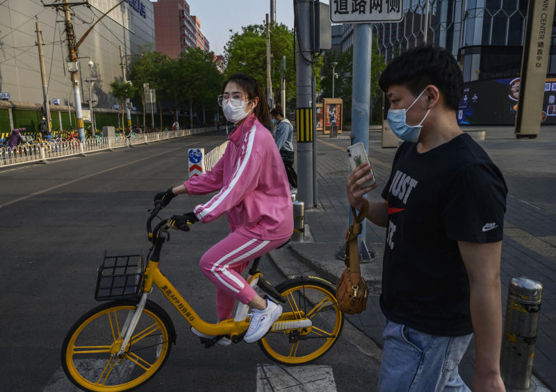 BEIJING, CHINA - APRIL 28: A Chinese woman wears a protective mask as she rides a bike in a shopping district on April 28, 2020 in Beijing, China. After decades of growth, officials said Chinas economy had shrunk in the latest quarter due to the impact of the coronavirus epidemic. The slump in the worlds second largest economy is regarded as a sign of difficult times ahead for the global economy. While industrial sectors in China are showing signs of reviving production, a majority of private companies are operating at only 50% capacity, according to analysts. With the pandemic hitting hard across the world, officially the number of coronavirus cases in China is dwindling, ever since the government imposed sweeping measures to keep the disease from spreading. Officials believe the worst appears to be over in China, though there are concerns of another wave of infections as the government attempts to reboot the worlds second largest economy. Since January, China has recorded more than 81,000 cases of COVID-19 and at least 3200 deaths, mostly in and around the city of Wuhan, in central Hubei province, where the outbreak first started. (Photo by Kevin Frayer/Getty Images)