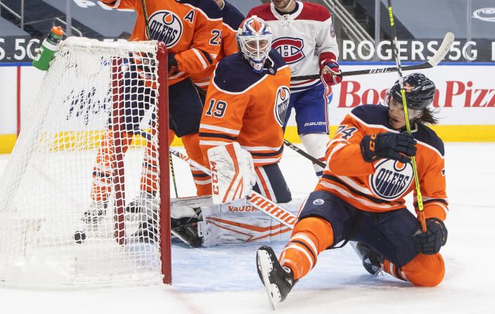 Edmonton Oilers' goalie Mikko Koskinen (19) is scored on as Ethan Bear (74) defends against the Montreal Canadiens during first-period NHL hockey game action in Edmonton, Alberta, Saturday, Jan. 16, 2021. (Jason Franson/The Canadian Press via AP)