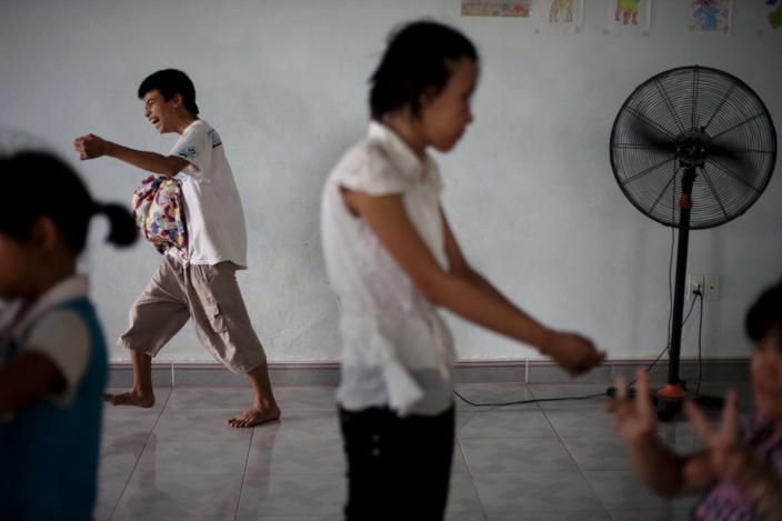 In this photo taken on Aug. 7, 2012, Dang Cong Kien, 18, rear, and Dang Thi Khanh Mai, 17, center in foreground, prepare for a nap at a rehabilitation center in Danang, Vietnam. The children were born with physical and mental disabilities that the center's director said were caused by their parents' exposure to the chemical dioxin in the defoliant Agent Orange. Washington was slow to respond, but on Thursday, Aug. 9, 2012 the U.S. for the first time will begin cleaning up leftover dioxin that was stored at the former military base, now part of Danang's airport. (AP Photo/Maika Elan)