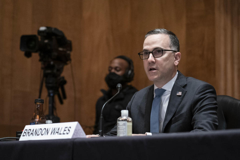 Brandon Wales speaks into a microphone at a hearing