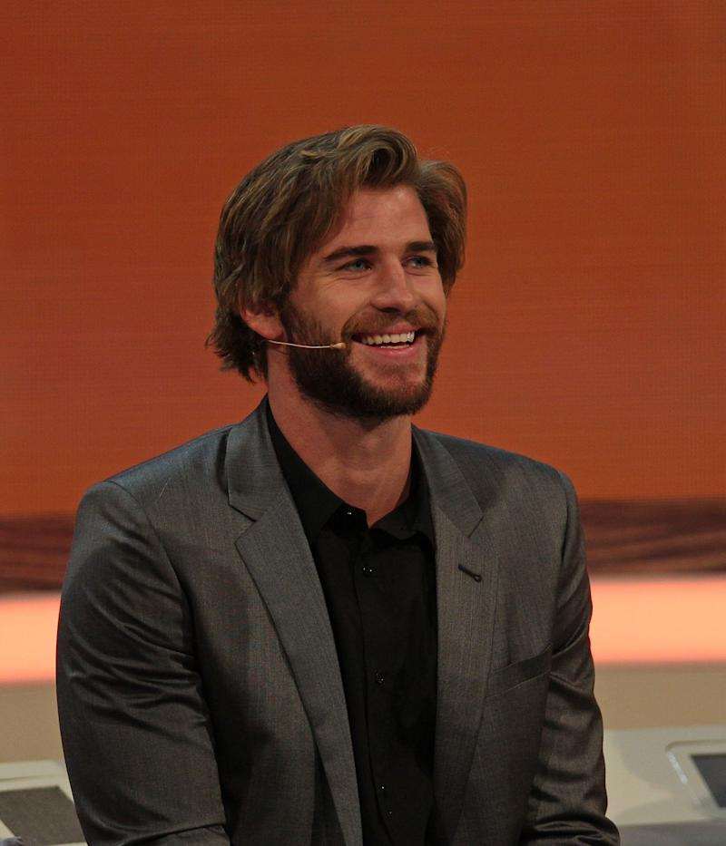Liam Hemsworth sports a grey colored suit and pant to match with a black inner T-shirt during an interview