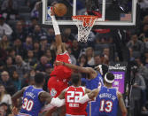Sacramento Kings guard Buddy Hield, top, goes up to stuff against New York Knicks center Mitchell Robinson, background, right, during the first quarter of an NBA basketball game in Sacramento, Calif., Friday, Dec. 13, 2019. (AP Photo/Rich Pedroncelli)