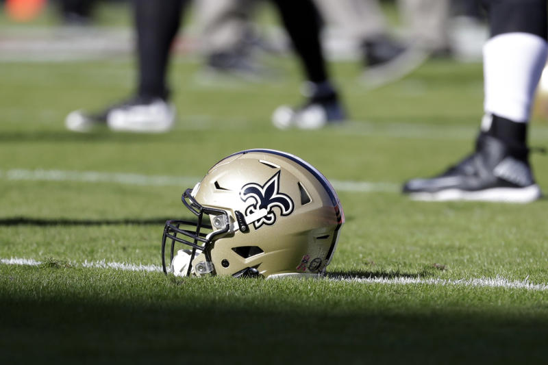 FILE - In this Oct. 23, 2016, file photo, a New Orleans Saints helmet rests on the playing field before an NFL football game in Kansas City, Mo. An Associated Press review of public tax documents found that the Bensons' foundation has given at least $62 million to the Archdiocese of New Orleans and other Catholic causes over the past dozen years, including gifts to schools, universities, charities and individual parishes.  (AP Photo/Jeff Roberson, File)
