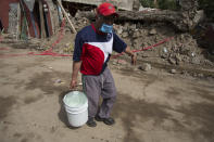 <p>A neighbor carries a bucket of water in San Gregorio Atlapulco, Mexico, Friday, Sept. 22, 2017. The water service still does not work, fourth day after Tuesday's major earthquake that devastated Mexico City and nearby states. (AP Photo/Moises Castillo) </p>