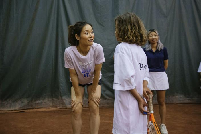 Two-time Grand Slam champion Li Na talks to one of the students during the clinic she led at the Sutton East Tennis Club Thursday, July 18, 2019, in New York. Li Na will be inducted into the Tennis Hall of Fame on Saturday, July 20. (AP Photo/Kevin Hagen)