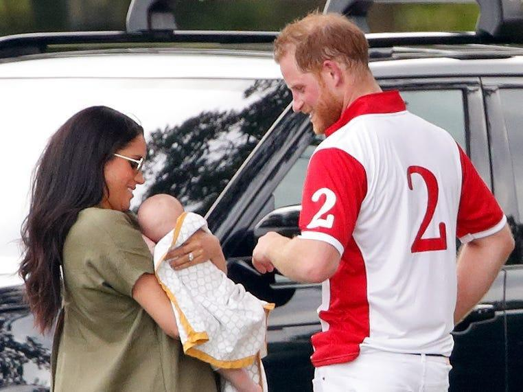 Meghan Markle, holding Archie, talks with Prince Harry while standing outside a black car