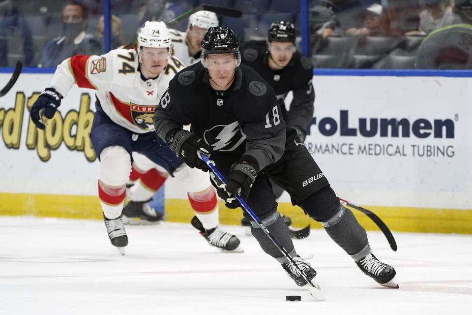 Tampa Bay Lightning left wing Ondrej Palat (18) starts the break out ahead of Florida Panthers right wing Owen Tippett (74) during the second period of an NHL hockey game Saturday, April 17, 2021, in Tampa, Fla. (AP Photo/Chris O'Meara)
