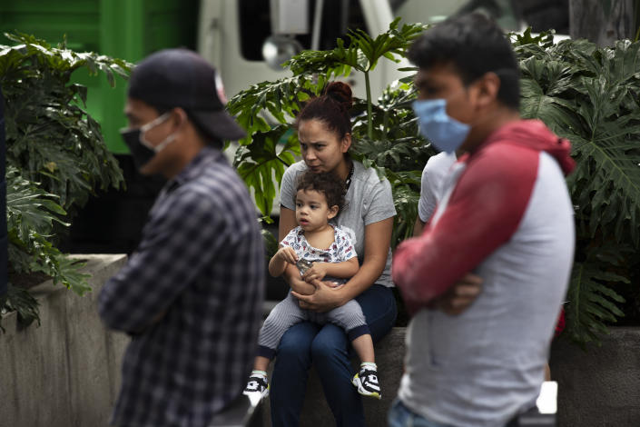 A woman sits with her son outside home as they wait until it is called safe to return to their apartment, after an earthquake in Mexico City, Tuesday, June 23, 2020. The earthquake struck near the Huatulco resort in southern Mexico on Tuesday morning, swayed buildings in Mexico City and sent thousands fleeing into the streets. (AP Photo/Marco Ugarte)