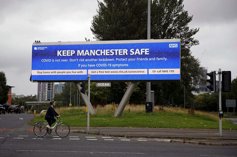 A woman rides a bicycle past a sign about the spread of the coronavirus disease (COVID-19), in Manchester, Britain, August 1, 2020: REUTERS