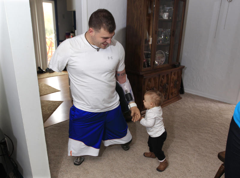 Army Staff Sgt. Travis Mills plays with his daughter Chloe in his boyhood home in Vassar, Mich., Thursday, Oct. 4, 2012. Mills is visiting his hometown for the first time since losing all four limbs while fighting in Afghanistan. Mills, his wife, Kelsey, and their 1-year-old daughter, Chloe, will be the grand marshals of Vassar High School's homecoming parade on Thursday evening. (AP Photo/Carlos Osorio)