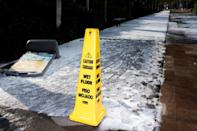 A caution sign is placed on a snow covered sidewalk in Houston, Texas on February 15, 2021