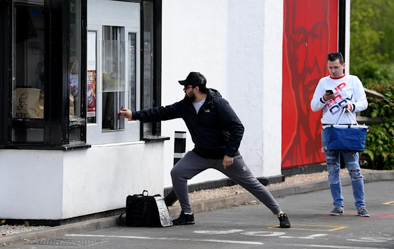 LEICESTER, ENGLAND - MAY 02: A man tries to keep his distance while showing his phone to the staff as he picks up food from the KFC restaurant take-out booth on Narborough Road, Leicester on May 02, 2020 in Leicester, England. British Prime Minister Boris Johnson, who returned to Downing Street this week after recovering from Covid-19, said the country needed to continue its lockdown measures to avoid a second spike in infections. (Photo by Ross Kinnaird/Getty Images)