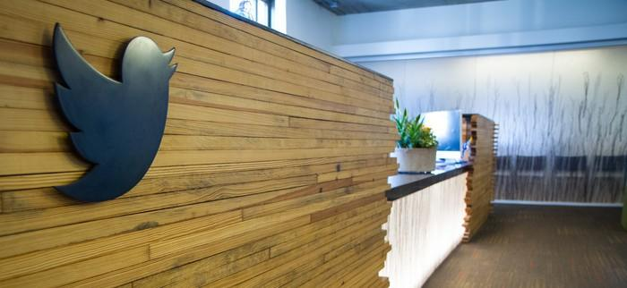 The Twitter logo on the front of a reception desk.