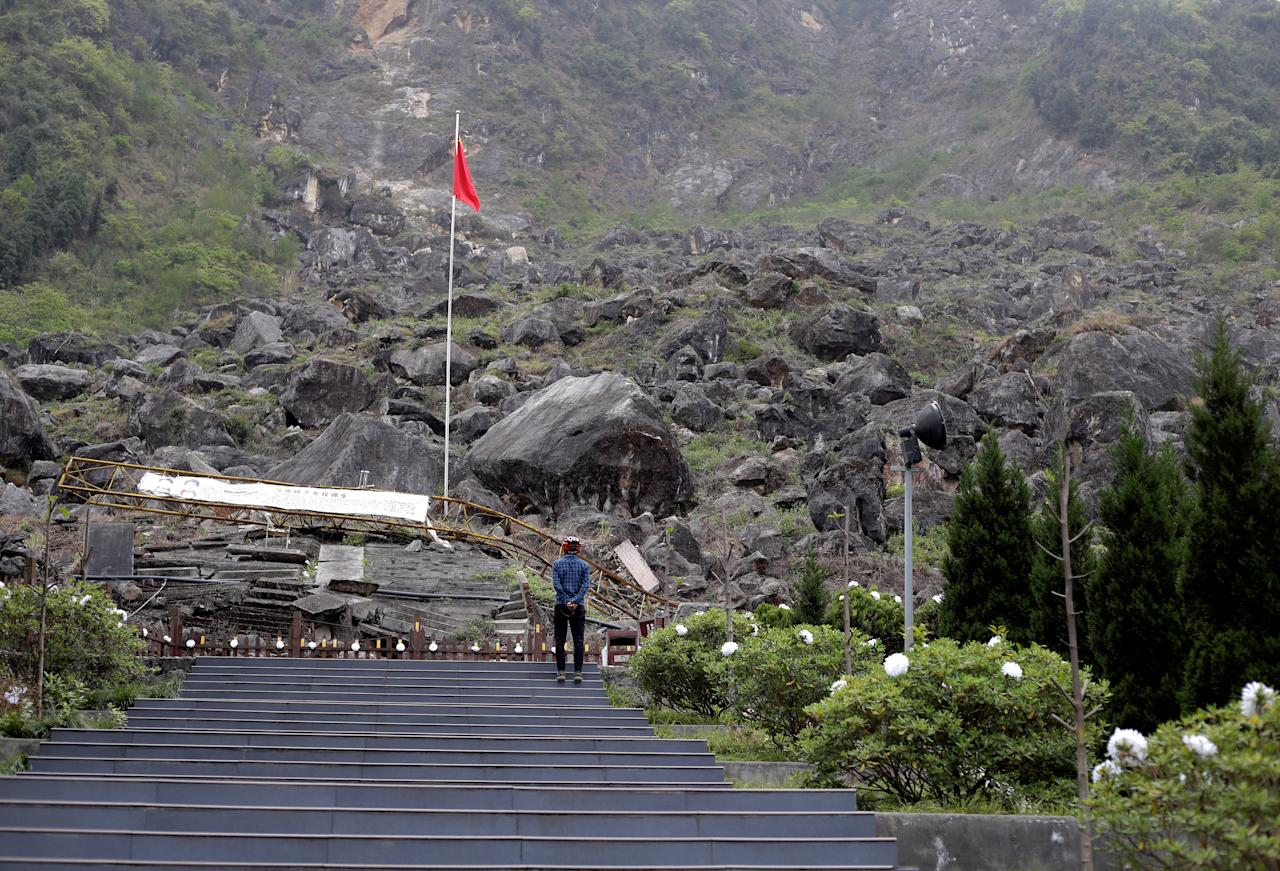 "A visitor stands in front of the site of Beichuan Middle School which was buried by boulders in the 2008 Sichuan earthquake, in the city of Beichuan, Sichuan province, China, April 6, 2018. REUTERS/Jason Lee  SEARCH ""BEICHUAN ANNIVERSARY"" FOR THIS STORY. SEARCH ""WIDER IMAGE"" FOR ALL STORIES."