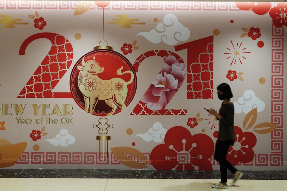 A shopper passes by Chinese New Year decorations at a shopping mall in Singapore's Marina Bay area. (PHOTO: Getty Images)