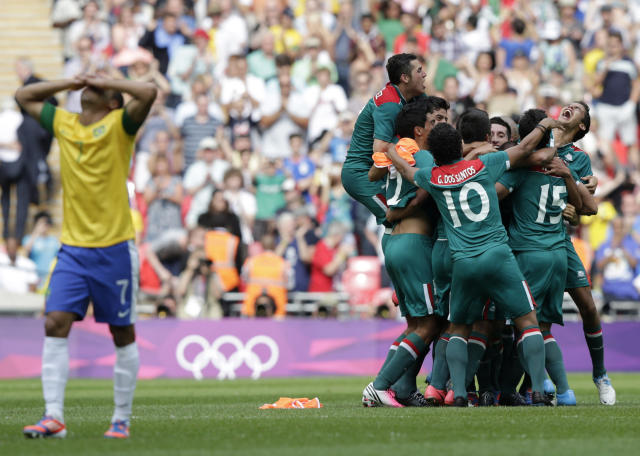 Brazil's Lucas (L) reacts as Mexico's players celebrate their victory over Brazil after their men's soccer final gold medal match at Wembley Stadium during the London 2012 Olympic Games August 11, 2012. REUTERS/Toru Hanai (BRITAIN - Tags: SPORT SOCCER OLYMPICS TPX IMAGES OF THE DAY)