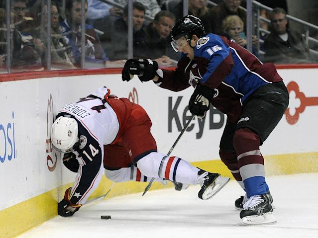Columbus Blue Jackets left wing Blake Comeau, left, is checked against the boards by Colorado Avalanche defenseman Cory Sarich, right, during the second period of an NHL hockey game Tuesday, Dec. 31, 2013, in Denver. (AP Photo/Chris Schneider)