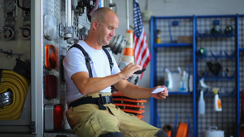 Fireman depositing check with mobile phone at the fire station.
