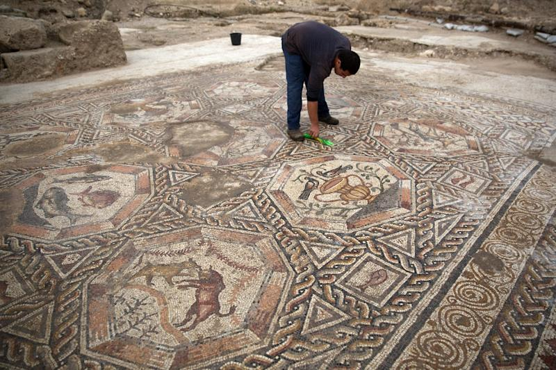A worker of the Israel Antiquities Authority cleans a 1,700-year-old mosaic, which served as pavement for the courtyard in a villa during the Roman and Byzantine periods on November 16, 2015, in the Israeli central city of Lod