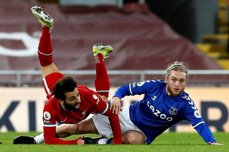 Mohamed Salah (L) of Liverpool and Tom Davies of Everton fall at Anfield during the Merseyside derby