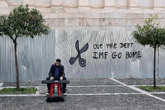 """A man plays music on a digital keyboard near graffiti on a corrugated metal gate reading """"Cut the debt, IMF go home"""" in Athens on February 24, 2015 (AFP Photo/Louisa Gouliamaki)"""