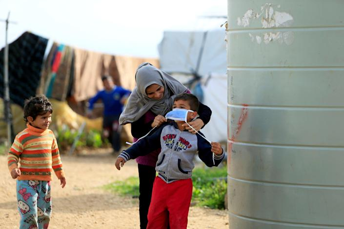 Syrian refugee woman puts a mask on her child in southern Lebanon (REUTERS)