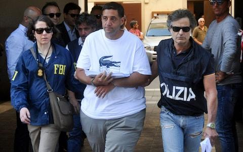 A US Federal Bureau of Investigation (FBI) officer (L) and Italian police officer (R) escort Thomas Gambino after he was arrested in Palermo during an police/FBI operation called 'New Connection' in Palermo on July 17, 2019 - Credit: AFP
